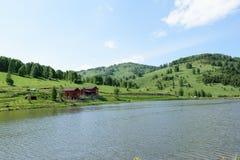 Casa de madera en la orilla de un lago de la montaña en un verano soleado d imagen de archivo