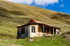 Casa de madera en la parte inferior de la montaña Imagenes de archivo