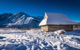 Casa de madera en montañas del invierno Imagen de archivo libre de regalías