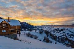 Casa de madera en una cuesta de montaña en la Navidad azul de la nieve hhory de Fotografía de archivo