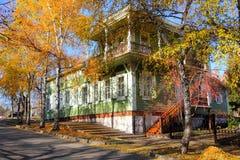 Casa de madera entre los árboles del otoño Fotos de archivo libres de regalías