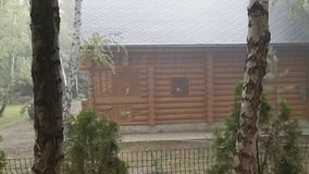 Casa de madera de la cabaña del país del registro en el temporal de lluvia pesado con el viento, el trueno y el relámpago Humor d metrajes