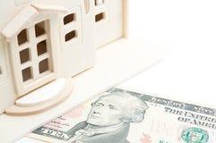 Casa de madera miniatura del juguete en el billete de dólar 10 Fondo blanco Fotografía de archivo