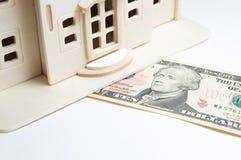 Casa de madera miniatura del juguete en el billete de dólar 10 Fondo blanco Fotos de archivo