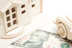 Casa de madera miniatura del juguete y coche de madera del juguete en el billete de dólar 10 Imagen de archivo