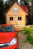 Casa de madera moderna y coche rojo Foto de archivo