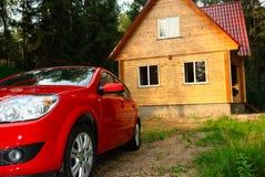 Casa de madera moderna y el coche rojo Imagen de archivo