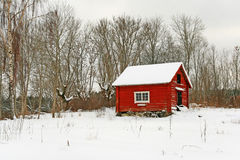 Casa de madera roja sueca tradicional en nieve Foto de archivo