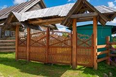 Casa de madera rural en pueblo con el gat tallado de la entrada Fotografía de archivo libre de regalías