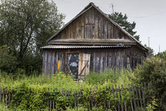 Casa de madera vieja con la cerca herbosa Mansión pobre del pueblo con de Op. Sys. Imagenes de archivo