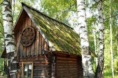 Casa de madera vieja en el bosque entre abedules en el campo ruso Imagen de archivo libre de regalías