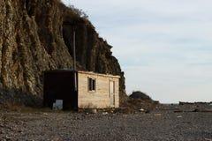 Casa de madera vieja en el fondo de rocas Fotografía de archivo