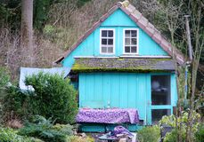 Casa de madera vieja linda en azul claro con las tejas de tejado rojas 2 fotos de archivo libres de regalías