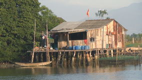 Casa de madera vietnamita en los zancos que se colocan en el río metrajes