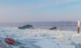 Casa de madera y dos barcos atrapados en el río congelado Foto de archivo libre de regalías