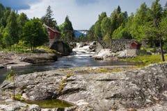 Casa de madera y un puente sobre un arroyo Imágenes de archivo libres de regalías