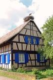 Casa de marco Alsatian con la jerarquía de una cigüeña en el tejado fotografía de archivo
