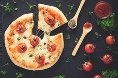 A casa de Margherita fez a pizza Vista superior na tabela escura imagem de stock
