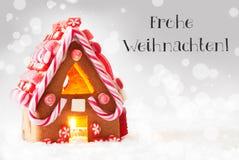 A casa de pão-de-espécie, fundo de prata, Frohe Weihnachten significa o Feliz Natal Imagem de Stock Royalty Free
