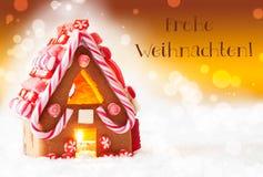 A casa de pão-de-espécie, fundo dourado, Frohe Weihnachten significa o Feliz Natal Fotografia de Stock Royalty Free