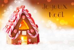 Casa de pão-de-espécie, fundo dourado, Joyeux Noel Means Merry Christmas imagens de stock royalty free