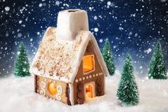 Casa de pão-de-espécie na neve com flocos de neve e fundo azul Imagem de Stock Royalty Free