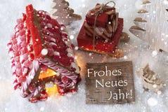 A casa de pão-de-espécie, trenó, flocos de neve, Frohes Neues significa o ano novo feliz Fotografia de Stock