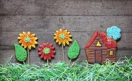 Casa de pão-de-espécie com flores e grama de papel em de madeira rústico Fotografia de Stock Royalty Free