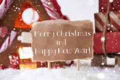 Casa de pan de jengibre con el trineo, los copos de nieve, la Feliz Navidad y el Año Nuevo Imagenes de archivo