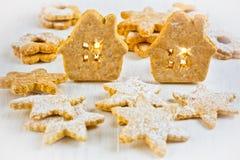 Casa de pan de jengibre de la Navidad, estrellas y galletas del linzer en el fondo de madera blanco, luz de la vela, plantilla de Fotografía de archivo libre de regalías