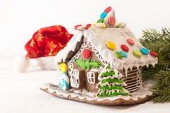 Casa de pan de jengibre de la Navidad, sombrero Santa Claus en blanco Fotografía de archivo libre de regalías
