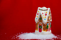 Casa de pan de jengibre en nieve en fondo rojo Fotografía de archivo