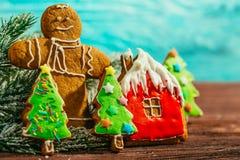 Casa de pan de jengibre pintada, árbol de navidad y el hombre en un fondo azul Foto de archivo libre de regalías