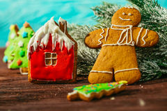 Casa de pan de jengibre pintada, árbol de navidad y el hombre en un fondo azul Fotografía de archivo libre de regalías