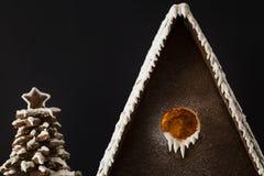 Casa de pan de jengibre y árbol bajo cierre de la nieve para arriba foto de archivo