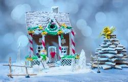 Casa de pan de jengibre y árbol de navidad cerca de un muñeco de nieve de la masilla del azúcar Fotografía de archivo libre de regalías