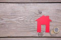 Casa de papel roja con el tejado rojo, con las monedas en fondo gris fotos de archivo libres de regalías