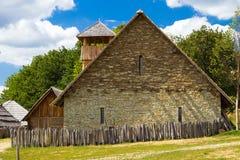 Casa de pedra atrás de uma cerca de madeira na exploração agrícola rural Foto de Stock