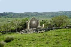 Casa de pedra caída velha no campo verde, ruína na natureza fotografia de stock royalty free