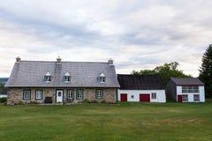 Casa de pedra com celeiro e a casa de galinha de madeira na ilha de Orleans Fotografia de Stock