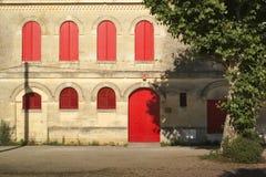 Casa de pedra com os obturadores fechados vermelhos Fotos de Stock