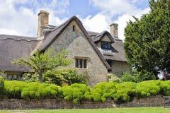 Casa de pedra inglesa com chaminés em uma vila rural imagem de stock