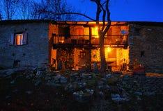 Casa de pedra velha da montanha no anoitecer fotos de stock royalty free