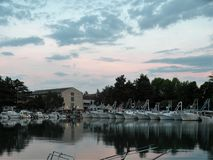 A casa de pedra velha de Istrian, em um córrego constante da água, com muitos barcos no porto na obscuridade com uma reflexão mag fotos de stock