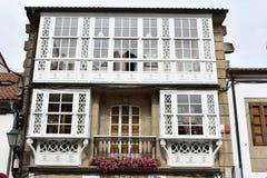 Casa de piedra con la galería de madera blanca, las flores rosadas, el balcón y la barandilla negra del hierro Santiago de Compos fotos de archivo