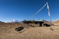 Casa de piedra con las banderas coloreadas en un fondo de las montañas, Himalaya, Nepal Imagen de archivo libre de regalías