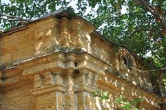Casa de piedra destruida amarilla antigua vieja en la yarda con los árboles alrededor Pobreza y miseria, del sur, verano fotografía de archivo libre de regalías