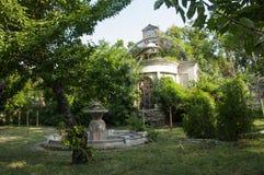 Casa de piedra destruida blanca antigua vieja en la yarda verde con los árboles alrededor Pobreza y miseria, del sur, verano foto de archivo libre de regalías