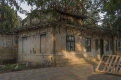 Casa de piedra destruida vieja en la yarda con los árboles alrededor Pobreza y miseria, del sur, verano imagenes de archivo