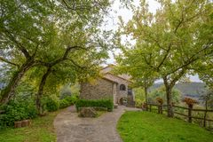Casa de piedra en el jardín verde con las flores imágenes de archivo libres de regalías